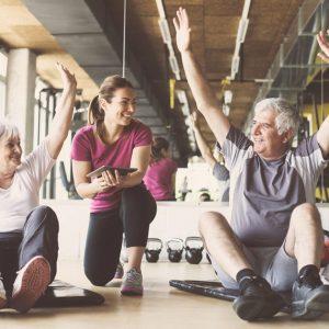 Idosos praticando exercícios físicos com ajuda de especialista | A importância dos exercícios físicos na terceira idade
