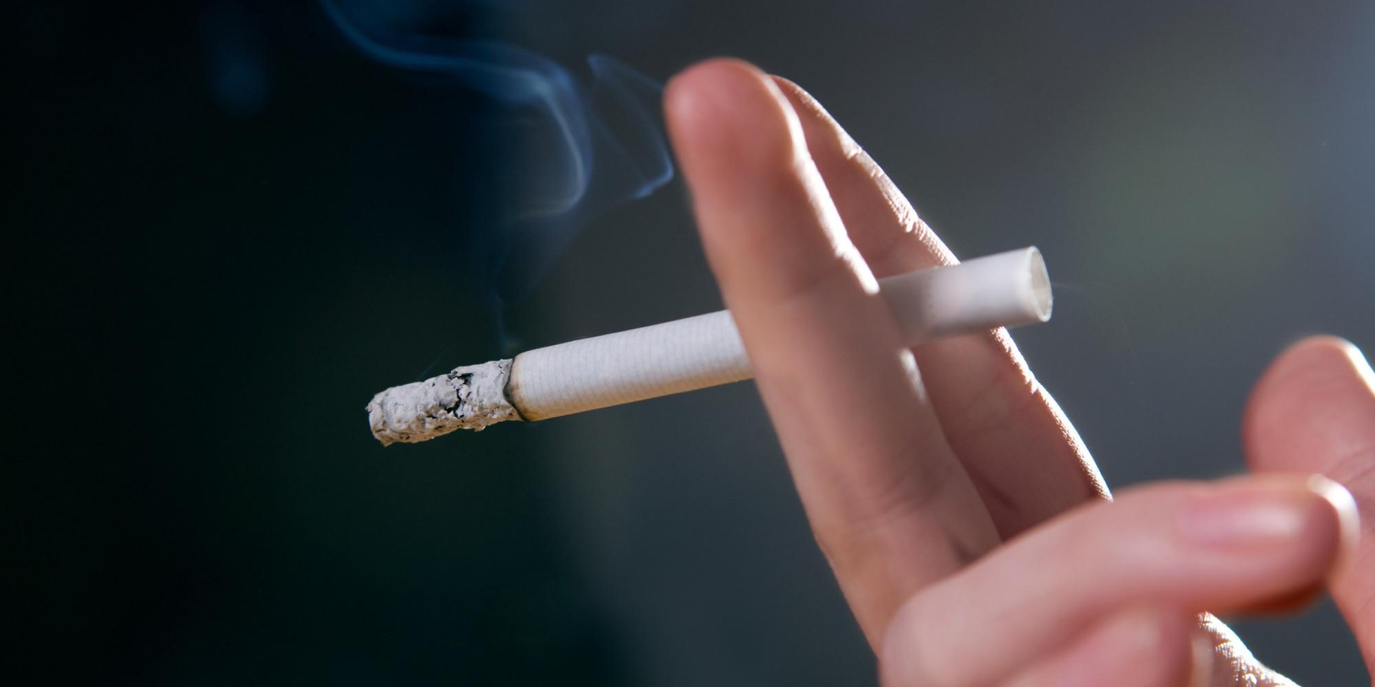 Mão femininas segurando cigarro aceso