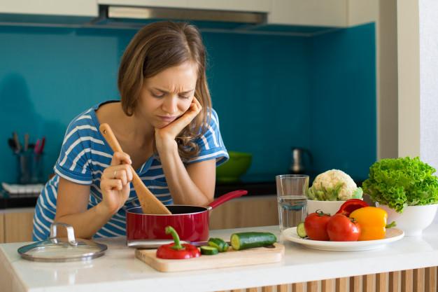 Mulher descontente que cozinha e que olha na bandeja