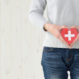Mulher segurando coração decorativo em frente a barriga